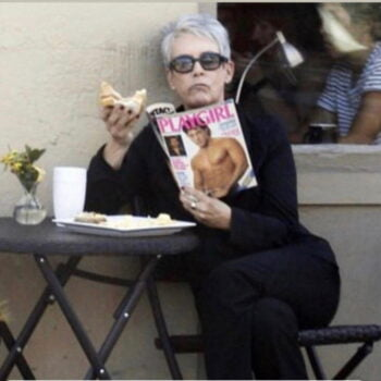 woman eating sandwich and reading Playgirl magazine