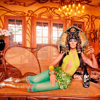 Christina Aguilera dressed in Egyptian headgear on chaise lounge with champagne