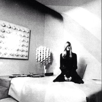 black and white image of Betty Catroux kneeling on bed in minimalist room
