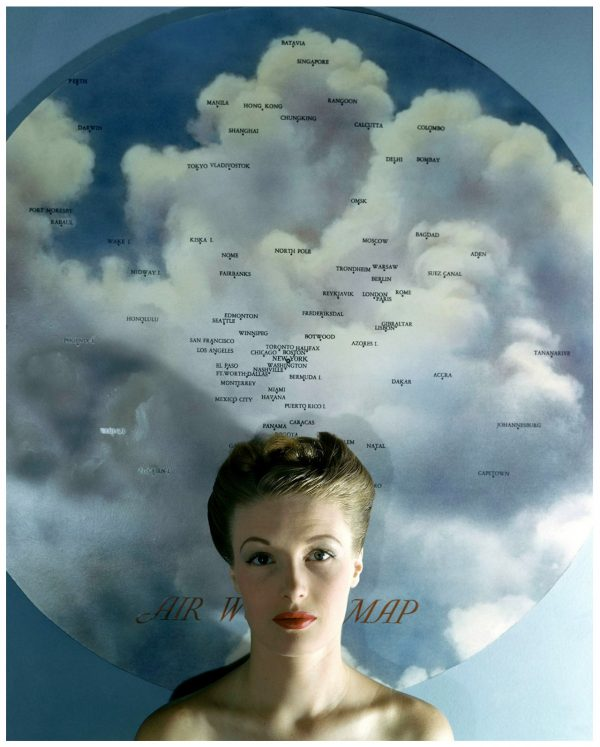 Vintage image of well-coiffed woman standing in front of a cloud map